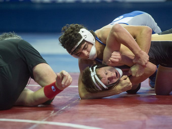 Job Greenwood of Poudre High School works to pin an