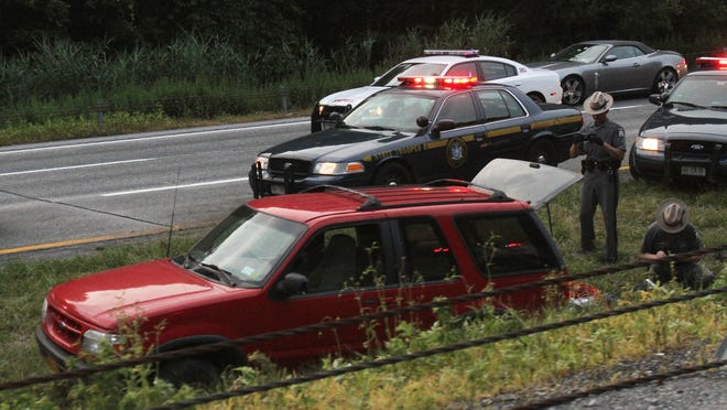 State troopers look over the red Ford SUV that was caught after a police chase southbound on Interstate 684 in Southeast Sunday.