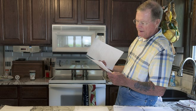 Chuck Zellers, of Lincoln, Neb., looks through some of the records and paperwork he has accumulated while trying to fix a Social Security error that declared him deceased.