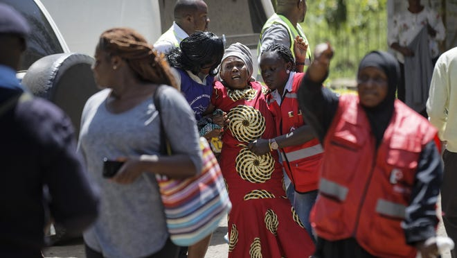 A unidentified relative is helped by Red Cross workers as she grieves after visiting the morgue in Nairobi, Kenya, Jan. 17, 2019. Extremists stormed a luxury hotel complex in Kenya's capital on Tuesday, setting off thunderous explosions and gunning down people at cafe tables in an attack claimed by Africa's deadliest Islamic militant group al-Shabab.