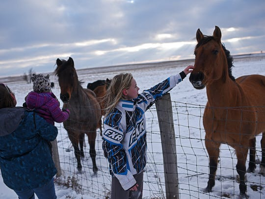 Makenzee, 12, pets one of her neighbors horses as her
