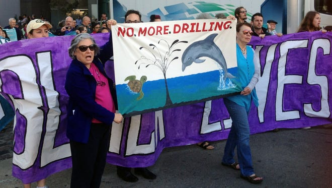 Environmentalists opposed to drilling in the Gulf of Mexico hold signs and chant slogans as they walk toward the Superdome to protest a federal government sale of oil and gas leases in the Gulf held in New Orleans, Wednesday, March 23, 2016. Federal officials say environmental protesters who demonstrated during the sale of oil and gas leases did not hold up the sale. Janice Schneider of the Department of Interior says no concerns were encountered about the protests Wednesday.