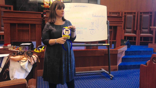 Rabbi Shana Goldstein Mackler explains the Hebrew symbols on the dreidel to a conversion class at The Temple in Belle Meade on Sunday, Dec. 6, 2015.