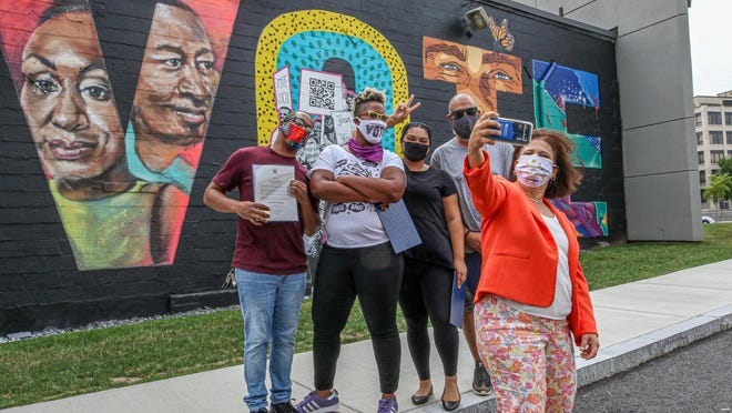 Rhode Island Secretary of State Nellie Gorbea takes a photo after presenting citations to, from left, Kendel Joseph (Lucid Traveler), Jessica Brown (The Lady J), Angie Gonzalez (Agonza) and Mikey Fernandez for their recent work on The Avenue Concept's VOTE mural. The mural is on the exterior wall of 1 Ship St. that faces the Point225 innovation center.