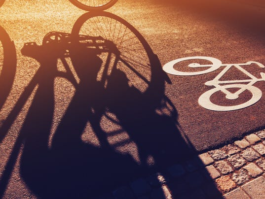 Shadow of unrecognizable cyclist riding a bike on bicycle lane
