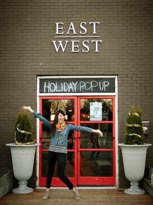 Nikki Whited poses in front of the East West Holiday Pop-Up Shop last year. The event returns this month.