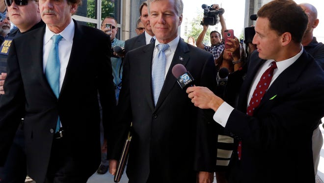 Former Virginia Gov. Robert F. McDonnell, center, with his attorney Henry W. Asbill, left, arrive at the federal courthouse in Richmond, Va., Monday, July 28, 2014, on the first day of jury selection in the corruption trial of McDonnell and his wife in Richmond, Va.