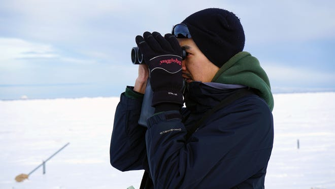Terrin Magby scans the sea ice from a hill above Wales, Alaska, during a polar bear patrol.