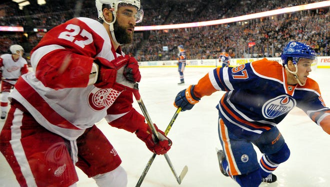 Red Wings defenseman Kyle Quincey (27) battles for the puck with Oilers center Connor McDavid (97) during the second period of the Wings' 3-1 loss Wednesday in Edmonton, Alberta.