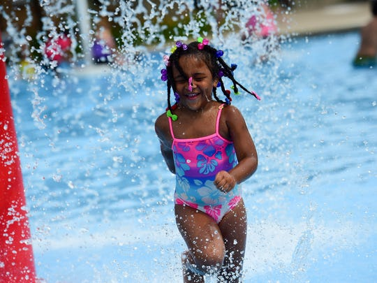 Emma Sacco, 4, laughs as she runs under a water fountain