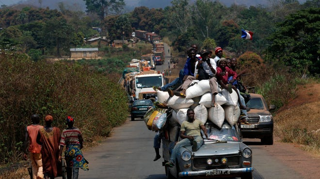 A vehicle filled with people and a heavy load precedes a convoy of over 100 trucks arriving in the Central African Republic capital Bangui from Cameroon on Jan. 27.