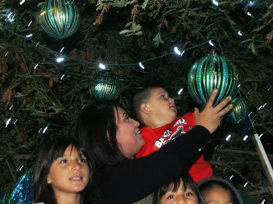 Karla Farias and her son Devin Perez, 2, check out a Christmas tree next to her daughter Hennessy Perez (left), 9, at The Collection in Oxnard. Families can take photos with Santa, who will be in hand through Christmas Eve.