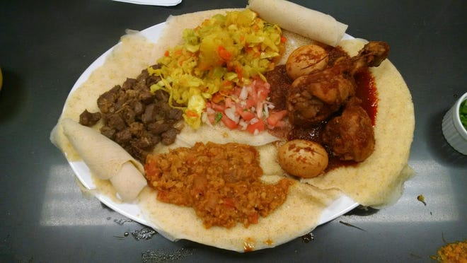 """All Ethiopian stews that I know of are served on and/or with injera, which is like a large spongy crepe; the injera functions as both your bread and your """"silverware."""""""
