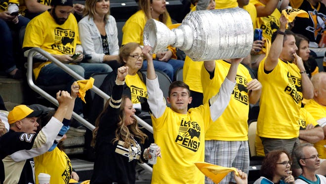A Pittsburgh Penguins fan hoists a fake Stanley Cup amid cheering mates during the playoffs.