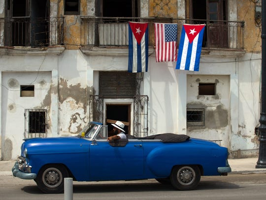 An old car passes by a house decorated with the flags