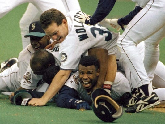 FILE - In this Oct. 8, 1995, file photo, Seattle Mariners' Ken Griffey Jr. smiles from beneath a pile of teammates who mobbed him after he scored the winning run in the bottom of the 11th inning of a baseball game against the New York Yankees in Seattle. Ken Griffey Jr. seems assured of election to the Baseball hall of Fame on the first try Wednesday, Jan. 6, 2016, possibly with a record vote of close to 100 percent. Mike Piazza, Jeff Bagwell and Tim Raines also were strong candidates to gain the 75 percent needed for baseball's highest honor.  (AP Photo/Elaine Thompson, File)