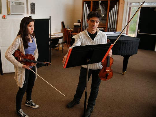 Yuliyan Stoyanov, right, talks with Madelyn Deininger, 15, a freshman at Walnut Hills High School, during a violin lesson, Thursday, March 24, 2016, at Holy Trinity Episcopal Church in Madeira, Ohio. Stoyanov, a Bulgarian-born violinist and College Conservatory of Music alumnus and current faculty member, faces deportation after two rejected appeals.