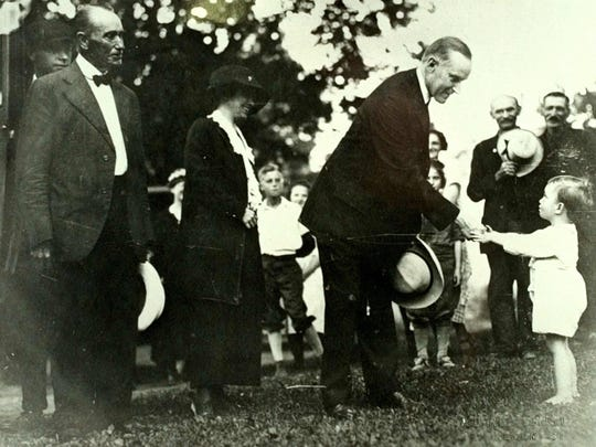 Calvin Coolidge gives a piece of candy to Jimmy Wilcox in 1923. Coolidge had just become president the night before. Coolidge's father and wife Grace are on the left.
