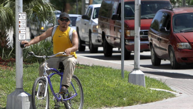 Bicyclist Antonio Morales, on his way home from work, pushes the crosswalk button at the Terry Street-Old U.S. 41 intersection in Bonita Springs Tuesday.