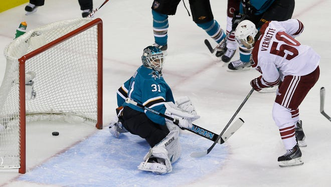 Arizona Coyotes center Antoine Vermette, right, scores a power play goal against San Jose Sharks goalie Antti Niemi, left, during the first period of an NHL hockey game Saturday, Nov. 22, 2014, in San Jose, Calif.