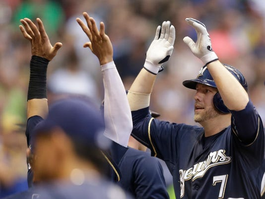Milwaukee Brewers' Mark Reynolds (7) gets high-fives in the dugout after his home run against the New York Mets during the sixth inning of a baseball game on Saturday, July 26, 2014, in Milwaukee. (AP Photo/Jeffrey Phelps)