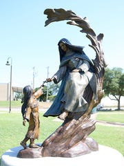 "The Lady in Blue, Sor Maria de Agreda, is depicted greeting a Jumano child in this bronze sculpture, which was set along the Concho River in San Angelo in 2018. A new production about her life, ""Lady of Agreda,"" is set to premier in Houston next March."