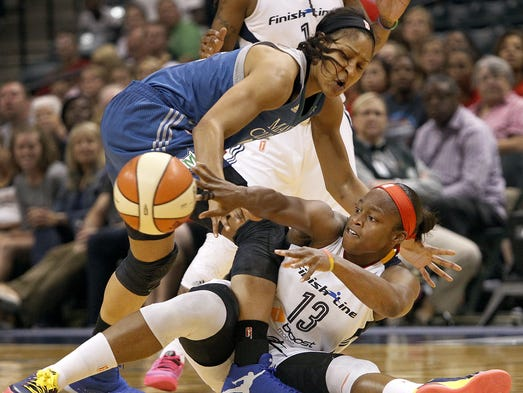 The Fever's Karima Christmas (13) passes around the legs of the Lynx's Maya Moore (23) in the first half of the Minnesota Lynx vs. Indiana Fever WNBA game at Banker's Life Fieldhouse in Indianapolis on Tuesday, Aug. 5, 2014. Indiana leads 44-38 at the half.