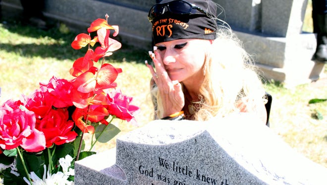 """Natasha Jasso wipes away tears at the grave site of her son, Ramon """"Momo"""" Pena III at Mountain View Cemetery during Saturday's seventh annual Rockin' The Streets Bike Run in memory of Momo."""