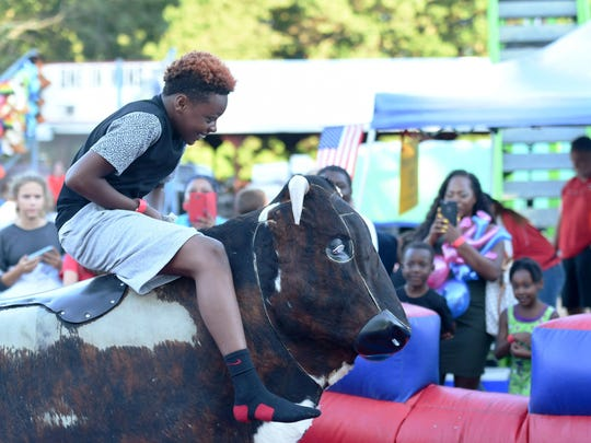 As'Ad Pompey, a Poughkeepsie native rides a mechanical bull as his aunt, Iberia Earth-Adams records video during the Ulster County Fair on Tuesday.