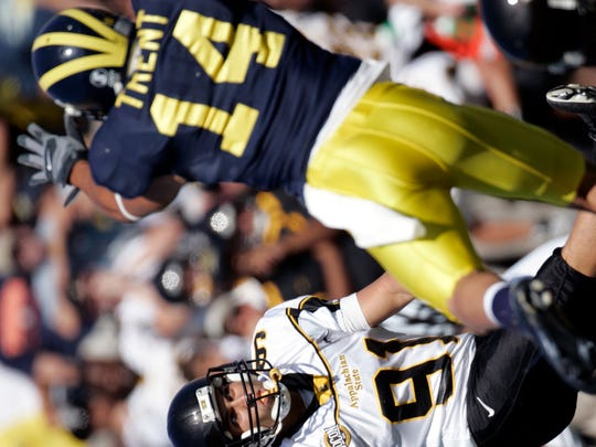 Appalachian State kicker Julian Rauch watches his 24-yard field goal, as Michigan cornerback Morgan Trent comes in late in an attempted block, that gave Appalachian State a 34-32 upset of Michigan on Sept. 1, 2007, in Ann Arbor, Mich.