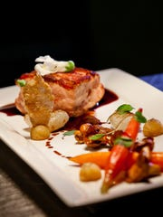 Chef Joane Garcia-Colson considers this Coq au Vin — crusted with bacon, and served with potato spheres, cippolini onions, baby carrots and roasted mushrooms in a red wine reduction— to be one of her signature dishes.