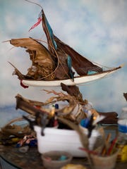 Just one of the many finished ships sit on display on Stosh's back porch. The ships are created out of plant materials and sea shells found in his yard. From palm leaves to pines Stosh will even use crab claws to decorate his ships.