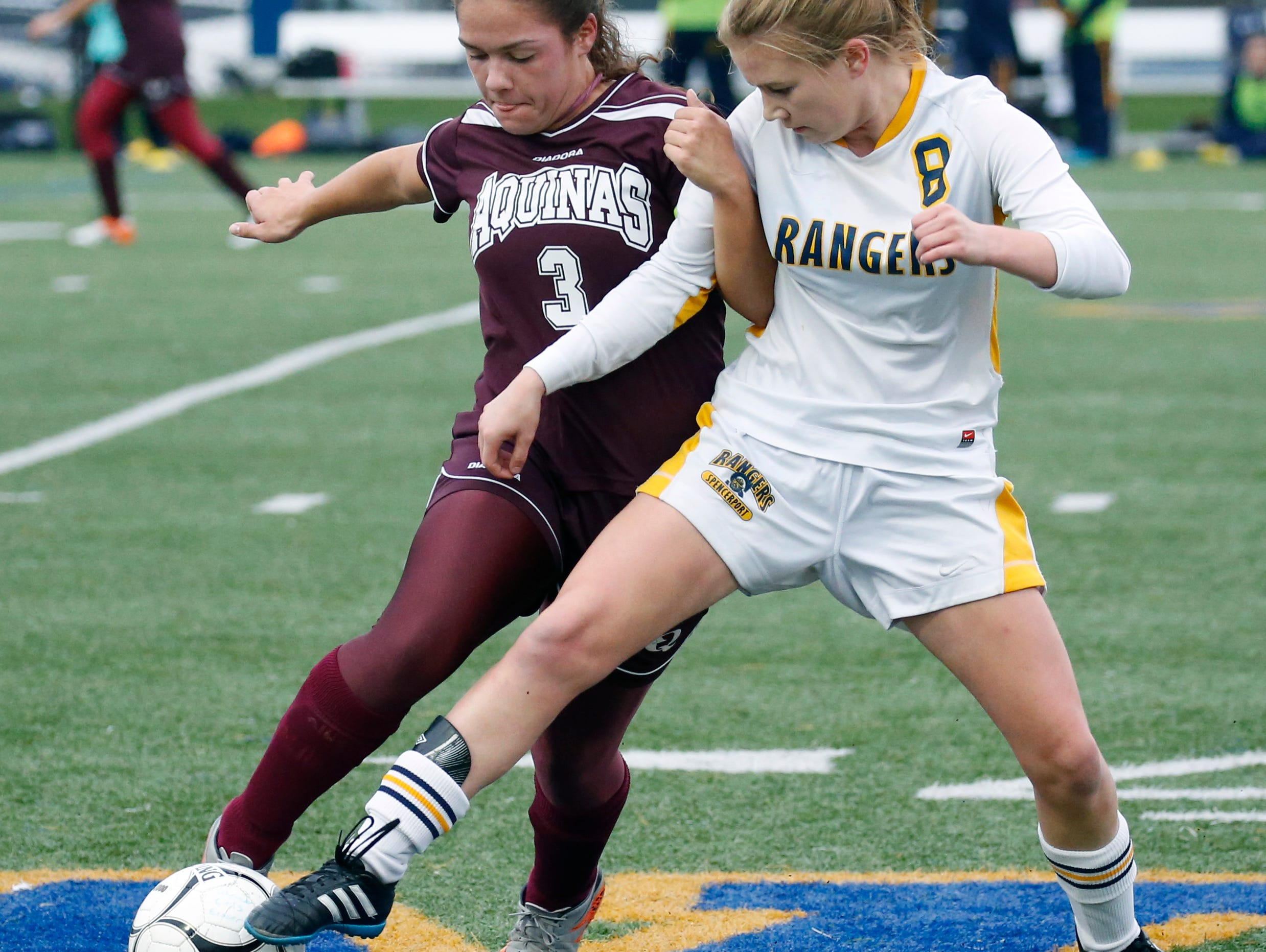 Aquinas' Gina DelMonche and Spencerport's Leah Wengender battle for the ball in the first half at Webster Schroeder High School.