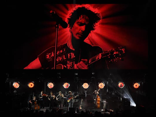 "Singer Ryan Adams performs with his band underneath an image of the late singer Chris Cornell during ""I Am The Highway: A Tribute to Chris Cornell"" at The Forum, Jan. 16, 2019, in Inglewood, Calif."