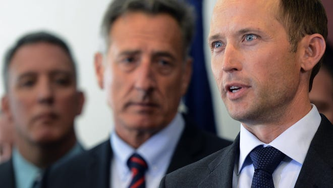 U.S. Attorney for the Vermont Eric Miller, right, speaks at a news conference Tuesday in Burlington as Gov. Peter Shumlin looks on. Miller and other state, federal and local officials gathered to announce federal charges for 12 people following statewide heroin-related investigations.