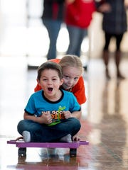 Adalynn Riddle, 6, pushes Mason Hinds, 4, toward a tumbling mat for a soft, crash landing at McGary Middle School Friday afternoon. Neighborhood kids were given a chance to play in the gym at the school and eat lunch in the cafeteria.