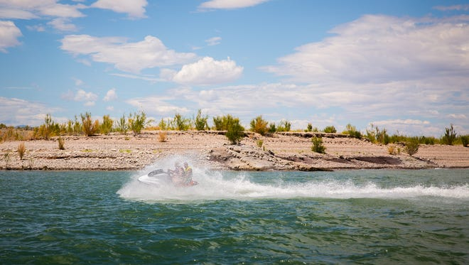 People ride a jet-ski on on Elephant Butte Lake, July 2, 2016.