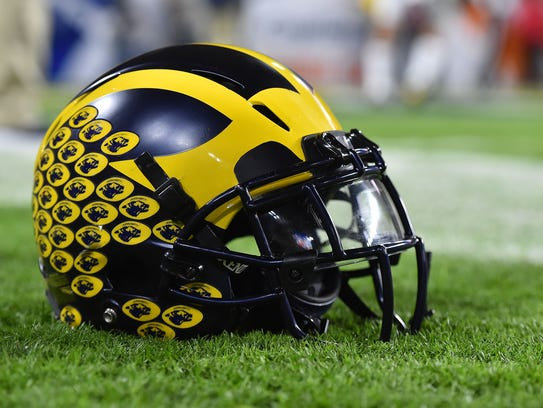 A Michigan Wolverines football helmet sits on the field