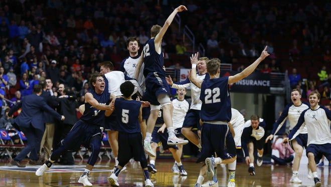 Members of the Xavier boys basketball team celebrate a 3A state championship win over Dubuque Wahlert on Saturday, March 12, 2016, at Wells Fargo Arena in Des Moines.