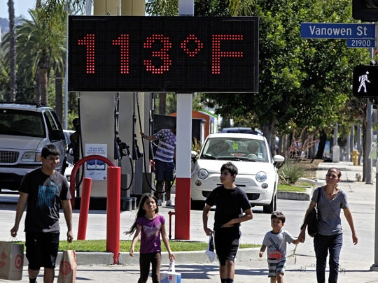 Pedestrians walk past a digital thermometer reading 113 degrees Fahrenheit in the Canoga Park section of Los Angeles in 2015.