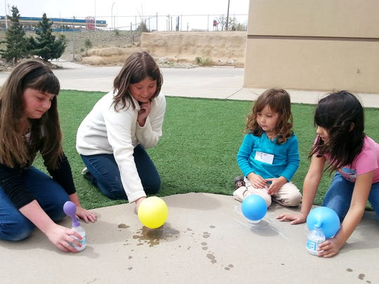 Cashlynn Claxton, Amelia Ellis, Rylee Reyes, and Ella Bertaloni blow up balloons using vinegar and baking soda during the Girl Scouts of the Desert Southwest Fun With Science program.