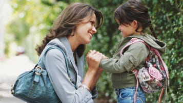 File photo --- Mother kneeling on pavement, holding hands of daughter (4-6 years), smiling, side view