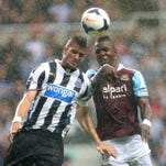 A Newcastle United player, left, and West Ham United player, right, strive for a header during the English Premier League soccer match at St James' Park, Newcastle, England, Saturday, Aug. 24, 2013.