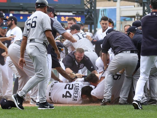 The Tigers' Miguel Cabrera (24) tangles on the ground