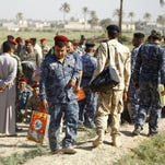 Iraqi militia members carry their belongings as they gather during the mobilisation of volunteer fighters in Hira, on September 22, 2014. 200 volunteers signed up to head to the front line to join in the fighting against the Islamic State (IS) group.
