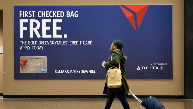 This file photo from March 24, 2015, shows a traveler passing a sign advertising a Delta Air Lines credit card at Seattle-Tacoma International Airport.