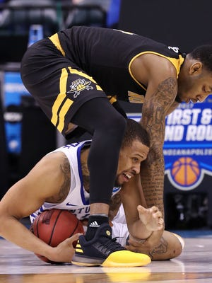 UK's Isaiah Briscoe (13) was a tied up NKU's Jeff Garrett (4) during the NCAA tournament at the Bankers Life Fieldhouse in Indianapolis.  Mar. 17, 2017