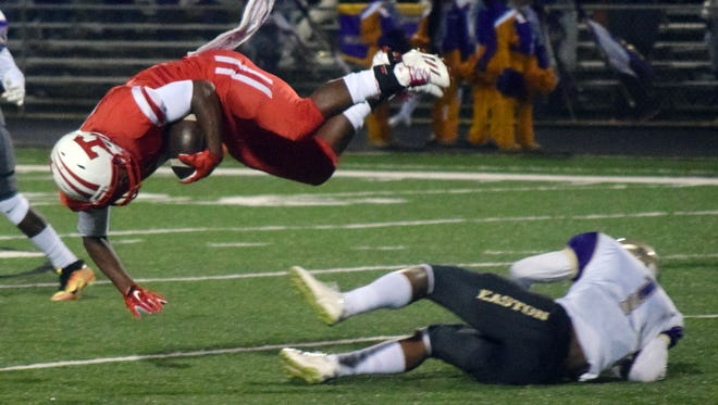 Tioga's Tre Allen (18, left) somersaults after being upended by Easton's Damien Tate, Jr., in a playoff game held Friday.