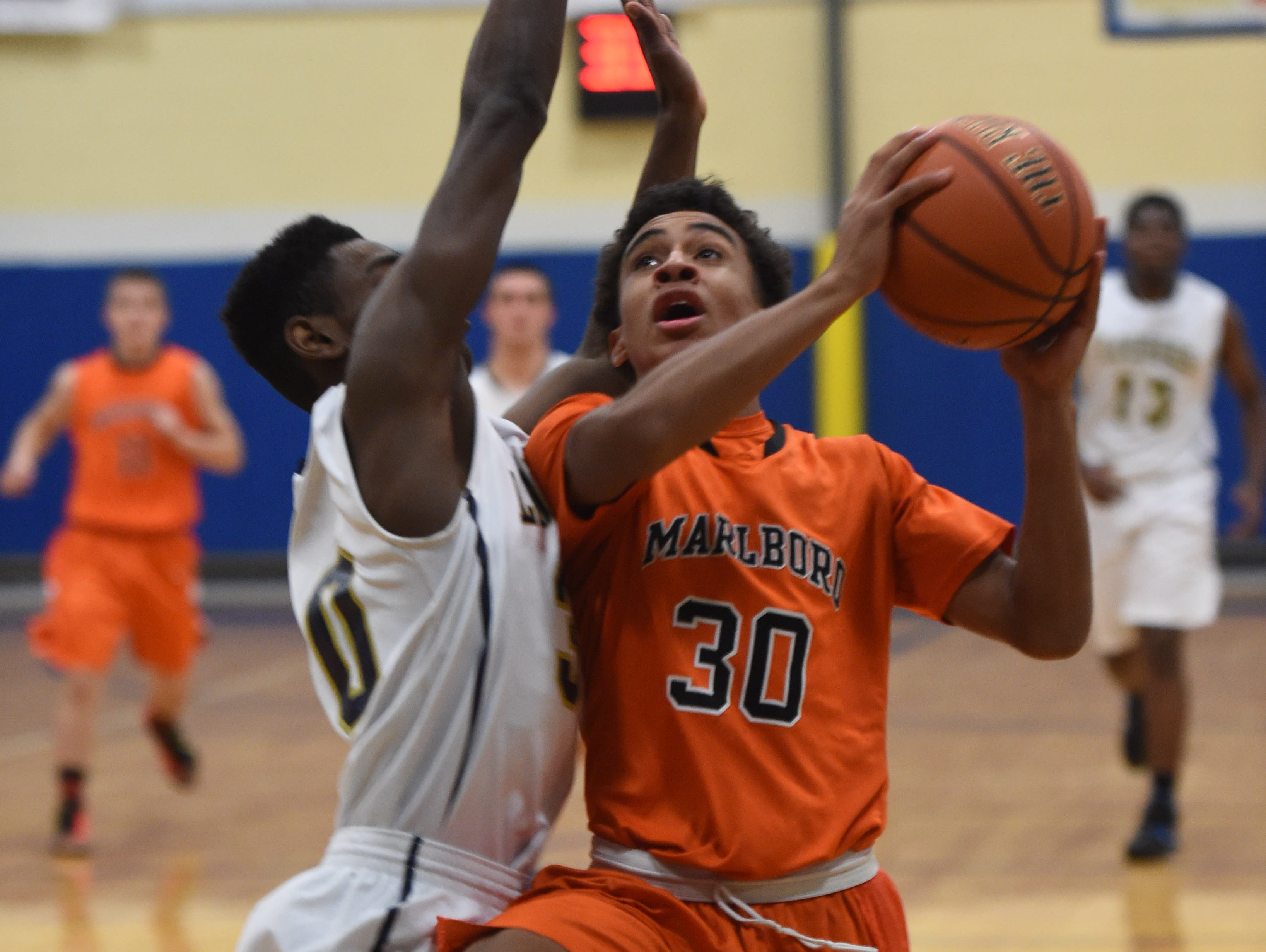 Marlboro High School's Jaiden Allen goes for a layup against Our Lady of Lourdes' Kevin Townes during the Duane Davis Memorial Holiday Tournament last December.