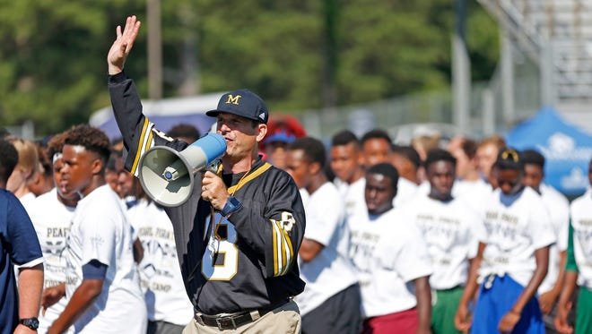 Michigan football coach Jim Harbaugh urges the more than 500 high school football players to listen to his explanation of a speed drill at a satellite camp June 8, 2016, in Pearl, Miss.
